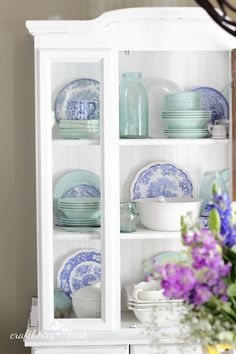 Blue and aqua decorations in a white hutch. Beach and summer colors. Just lovely.