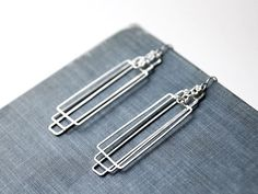A pair of earrings made of three (3) tiered rectangles, handmade from silver wire, inspired by the art deco era of the Great Gatsby movie. Its