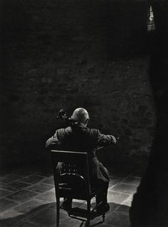 """Cellist Pablo Casals, 1954, by Yousuf Karsh, who said: """"I have never photographed anyone, before or since, with his back turned to the camera, but it seemed to me just right. For me, the bare room conveys the loneliness of the artist, at the pinnacle of his art, and also the loneliness of exile."""""""