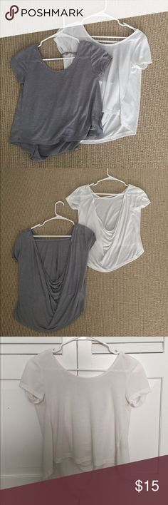 Two Cropped Open-Back Tees NWOT Two tees (one grey and one white) with a high-low design (high in the front and low in the back) and an open back with a strap across the top back to make sure the top doesn't fall off your shoulders. The white one was worn once and the grey was never worn. Buy both for $18 or one for $10 Tops Crop Tops
