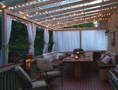 I love this look! I like the booth style seating, but I would only do an L shape. I would use it as storage for the cushions/pillows also. The lights over top is exactly what I am craving for a backyard dining area. The curtains double as a privacy thing and a pretty decoration.