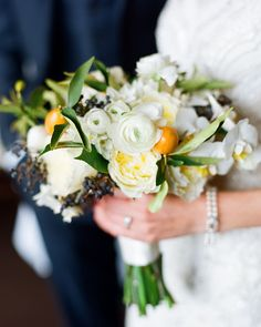 For an an unexpected element, this unique bouquet from Mimi Designs incorporated kumquats, as well as eskimo roses, privet berry, lisianthus, ranunculus, phaeleonopsis orchids, and camellia leaf. It highlighted the color palette of mostly grays and whites, with a pop of navy and orangey citrus.