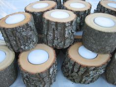 Centerpiece Idea... Large wood slices with candles (varying heights), let the wax drip on the wood. Wood cut in 2 inch slabs, about 12 inches round.