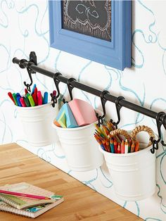 Hanging Out. Installing a towel rod with sliding hooks is an easy way to hang small buckets to organize crafts supplies. Storing colored pencils and pens on the wall makes it simple to find the right color!