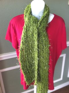 """A knit scarf in super soft green eyelash yarn. This is a gorgeous green that can accent many colors (black, brown, tan, white, purple, red, blue). The eyelash yarn is super warm without the bulk of a wool scarf.    This scarf can also be made in red, purple, champagne, black, and navy.    Length: approximately 66""""  Width: approximately 6""""  Care: hand wash and lay flat to dry or use Dryel bag to freshen"""
