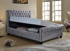 Flair Furnishings Lola Fabric Ottoman Silver Double | The Lola Fabric Bed Frame consists of a modern, sleigh style design with a cushioned and buttoned headboard which gives the bed frame a luxurious feel. This bed frame is available in a striking silver velour fabric, sure to catch the eye and be the focal point of any bedroom.