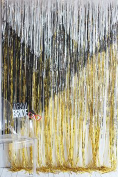 A quick, easy, and inexpensive DIY backdrop project for a modern, geometric wedding. Make this metallic fringe backdrop out of a few fringe curtains, some tape, and a pair of scissors. Anyone can do it! Perfect to use as a photobooth backdrop.