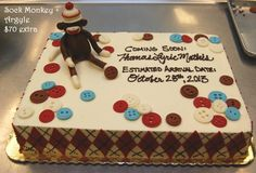 Sculpted sock monkey on a sheet cake decorated with buttons and an argyle pattern.