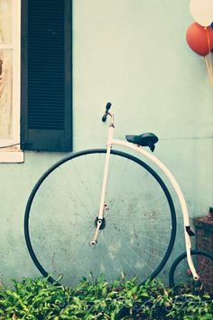 Fine art photograph. A Penny-Farthing bike leaning against a mint colored house with balloons peeking in the corner. Title: Penny Farthing