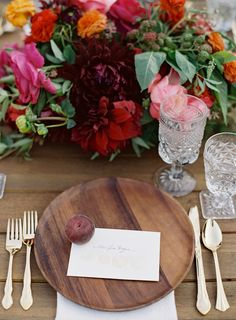 A great wooden charger adds a rustic vibe to a lush tablescape. I love the plum as a paperweight for the place card. Makes for a beautiful wedding table or a fall dinner party or a summer outdoor event!