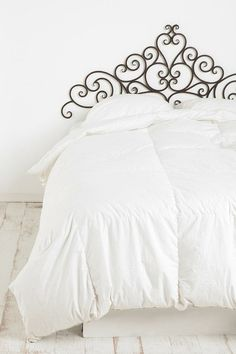 Snow white bedroom, accented by a wrought-iron headboard.