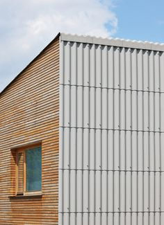 Corrugated fiber-cement panels wrap the roof and wall. Single-family House in Groharjevo / Wooden Facade, Metal Facade, Architecture Details, Interior Architecture, Facade Design, House Design, Open Living Area, Cladding, Home And Family