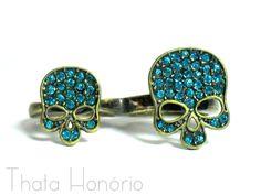 Cód: AN048  Tam: Dedo médio 18, dedo anelar 14.    Anel de caveira em ouro velho com strass azul....