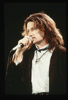 1985: U2's Bono sings into a microphone while onstage. He wears a brown leather, fringed jacket and a cross around his neck. (Photo by LGI Stock/Corbis/VCG via Getty Images)