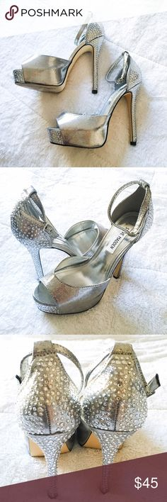 "Steve Madden Silver Platform Nairi Sandals Check my page for current promos and discounts! Open to reasonable offers. These were worn only once (bridesmaid outfit in a wedding); super comfortable! Let your evening look sparkle with the Steve Madden Nairi. These stunning rhinestone sandals have a delicate ankle strap and stiletto heel making them the ultimate platforms for your next event. Two-piece silver shimmer fabric upper Ankle strap with adjustable buckle 1¼"" platform, 5¼"" covered…"