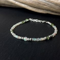Adorn yourself with Opals; composed of genuine Welo Opal Beads with hints of Peridot and Pyrite. All metal components in sterling silver. Delicate & Flashy!  ( $70)  #beadedbracelet #opaljewelry #braceletstack