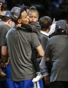 Steph Curry gives his daughter Riley a kiss after leading the Golden State Warriors to victory over the Cleveland Cavaliers in the 2015 NBA Finals.
