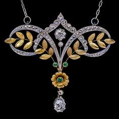 Belle Epoque Antique Diamond Emerald Platinum Gold Necklace, Circa 1910. An antique Edwardian era elegant garland-motif necklace is handcrafted in platinum and 18K gold. The necklace is embellished with brilliant and rose cut diamonds, and three small emeralds.