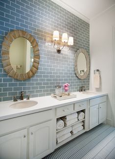 White and blue bathroom features scalloped oval mirrors on blue subway tile backsplash flanking Visual Comfort Lighting Vendome Triple Sconce over white double vanity paired with white speckled countertops and oval sinks. Bathroom features double vanity with open shelving over blue tiled floor.