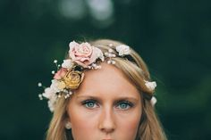 pastel pink + muted yellow silk flowers are weaved through ivory wooden flowers + babys breath.
