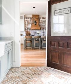Cute farmhouse kitchen from the perspective of the GORgeous laundry room complete with rustic zigzag red brick flooring. 💞💕💞 Love the open shelving on brick in the kitchen and the dramatic wood hood vent. Mudroom Laundry Room, Large Laundry Rooms, Laundry Decor, Laundry Room Design, Small Laundry, Home Design Diy, Küchen Design, House Design, Brick Flooring