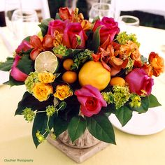 Summer arrangement with lemons & limes - - - think the flowers are spray roses, bupleurum, mokara orchids, and regular roses...