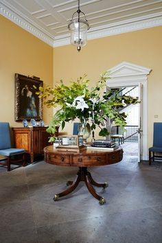 A striking floral arrangement sits on an antique drum table in the main hall of the Inchyra Estate.