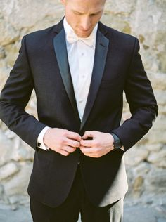 Black tuxedo with a white bow tie. Photography: JL Photographers