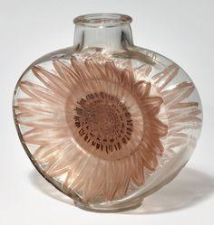 René LALIQUE (1860-1945) Vase Soleil Vase en verre blanc transparent à décor d'une fleur de tournesol patinée sépia et émaillé en son centre. Le décor est embossé dans chaque face du vase. Modèle créé en 1913  Hauteur: 20 cm