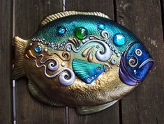 "Polymer clay and glass gems. The color comes from shimmery powdered pigments and metallic wax. This is the largest thing I have made to date! He is 15"" long...whew!"