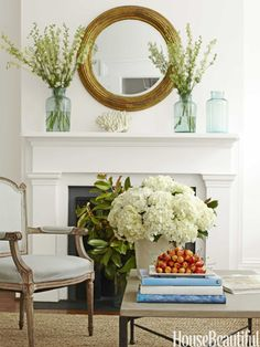 Round mirror above mantel. Design: Lynn Morgan. Photo: Christopher Baker. housebeautiful.com. #mirror #mantle #fireplace #livingroom #white