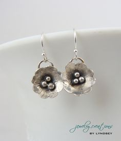 Antiqued sterling silver flower earrings. The flowers are hand forged.