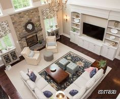 2 sitting areas. chairs and side table in front of fireplace and sectional/sofa area in front of tv. large rug tying whole room together with smaller rug on top to section off tv section