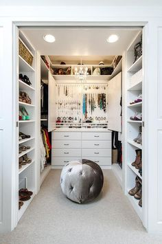 Perfectly organized white walk in closet features modular shoe cabinets facing inwards towards a gray velvet tufted pouf positioned on cream carpeted floors in front of a back wall lined with a dresser positioned below a custom jewelry cabinet fixed beneath handbag and hat shelves illuminated by a small chandelier.