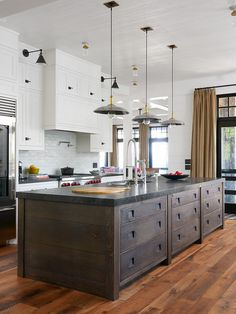 Wide shiplap kitchen island. Dark stained wide shiplap island. This farmhouse features stacked shaker cabinets, a dome kitchen hood and wide plank hardwood floors. It also features a dark brown salvaged wood kitchen island with stacked drawers and wide shiplap on the sides. The thick countertop is honed Belgian Bluestone. Farmhouse kitchen with dark shiplap island. Reclaimed wood shiplap. Wide shiplap kitchen island. Dark stained wide shiplap island. Farmhouse kitchen with dark shiplap…