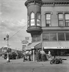 """August 1942. """"Dillon, Montana. Street corner. Dillon is the trading center for a prosperous cattle and sheep country."""" The cafe seen earlier here. Medium-format nitrate negative by Russell Lee for the Office of War Information."""