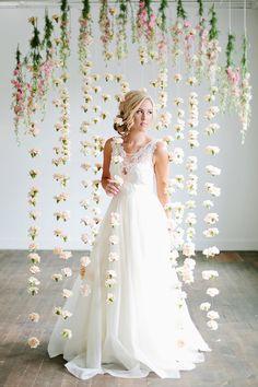 Bride posing in front of flower backdrop