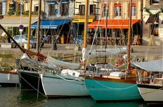 harbour scene with traditional fishing boats and harbour restaurants. Honfleur, Normandy, France.