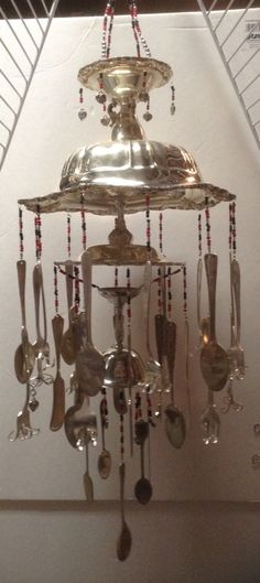 The photo is a little dark, but this is a wind chime made from silver plate serving dishes & cutlery. Keywords: windchimes, silver, silverplate, spoons, forks, silverware, silver dishes