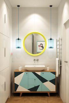 Круглое зеркало в желтой раме и тумба с геометрическим рисунком в ванной комнате