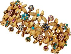 Multi-Stone, Diamond, Gold Bracelet The bracelet features round-cut rubies weighing a total of approximately 3.65 carats, enhanced by round-cut sapphires weighing a total of approximately 3.65 carats, complemented by turquoise cabochons measuring 2.00 - 2.75 mm, accented by single-cut diamonds weighing a total of approximately 0.50 carat, set in 18k gold. Gross weight 80.40 grams. Dimensions: 7-1/4 inches x 1-3/16 inches