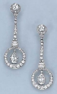 A PAIR OF ART DECO DIAMOND EAR PENDANTS. Each suspending an independently-set pear-shaped diamond, within a circular-cut diamond surround, from a baguette, old European and circular-cut diamond line, to the old European- and circular-cut diamond surmount, mounted in platinum, circa 1925.