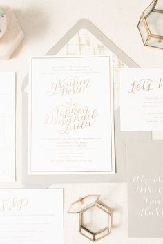 Romantic gold foil wedding invitations by Paper & Honey with whimsical calligraphy, a neutral color palette, and white calligraphy on gray envelopes