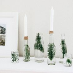Put pine sprigs in clear glass bottles, and top them off with candlesticks.