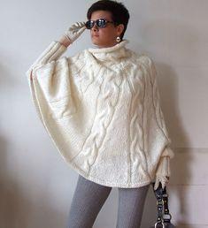 El poncho! La nueva moda favorita! El gran color de crema marfil.  Absolutamente seductor cuando remolinos alrededor del cuerpo con cada paso tome.  Sólo en esta belleza y mostrar sus piernas en pantalones pitillo o leggings y tacones.  tan elegante!  ¡ Siéntase como una celebridad en su propio poncho!  No omita los guantes. Añaden especias extra. ~~~~~~~~~~~~~~~~~~~~~~~~  Tejido a mano por cable poncho con cuello de cuello ancho.  Amplia puños coger el cabo en lados y mantenga alrededor de…