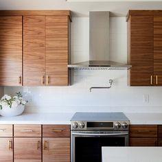 Stunning walnut kitchen cabinets, white counter, white backsplash, modern stainless appliances, brass hardware