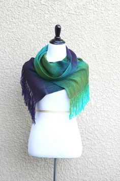 "Hand woven long scarf with gradually changing colors from green to purple. Amazing color shades and color variety. Measures: L: 78"" with 6"" fringe on both ends W: 11"" Care instructions: This scarf mad"