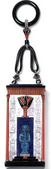 Egyptian Vanity Case, Cartier Paris, 1924 Gold, Platinum, Mother of Pearl Carved Hieroglyphs, Antique Blue Egyptian Faïence, Coral, Lapis Lazuli, Onyx, Diamonds, Black Enamel, Leather Cord, Interior Sliding Downward with a Folding Mirror, a Small Gold and Tortoiseshell Comb, and Two Covered Powder Compartments.