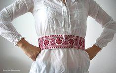 Textilný opasok s červenou krížikovou výšivkou na prednej strane. Zadaná strana biela, na zaväzovanie šnúrkami. Dĺžku opasku možno upraviť podľa požiadaviek, výšivkacca 40 cm....