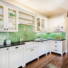 White and green kitchen.  I just love the earthy yet elegant combination of the green tiles and the dark wood floors.